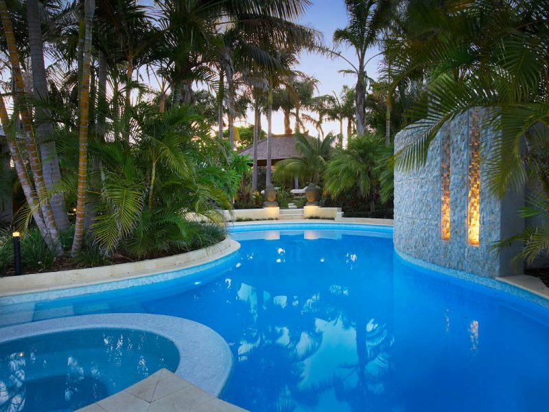 Turquoise blue kidney shape pool surrounded by lush tropical garden with palms that pavilion in rear with large stone busts and stone water feature with light channels the pool is tiled in white mosaic